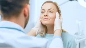a doctor examining the botox injection results performed on a womans face.