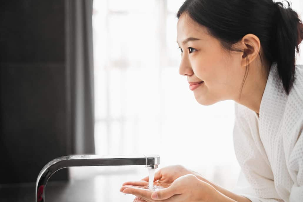 An Asian woman cleaning her face in a bathroom sink with water running on her hands as she smiles at her reflection.