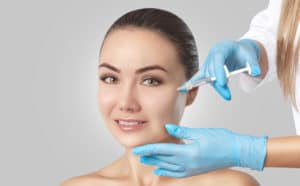 an image of a woman recieving a dermal fillers injection in her cheek. The background is a grey blank canvas, the doctor is wearing blue latex gloves.
