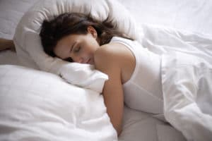 An image of a woman laying face down in her bed with white covres over her.