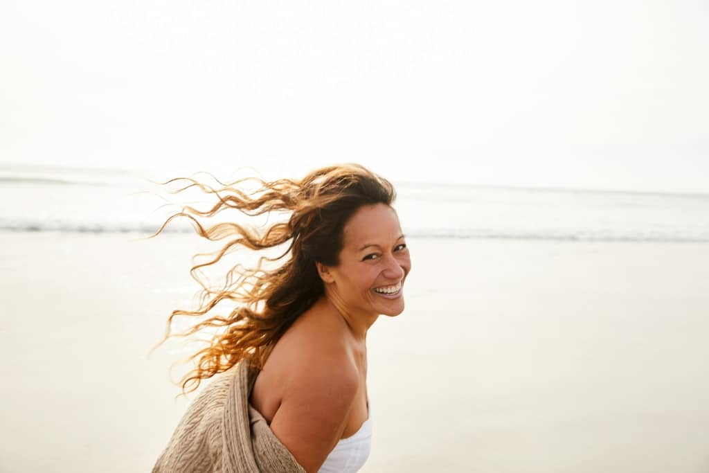 laughing mature woman walking on a beach on a breezy afternoon picture id1217412013